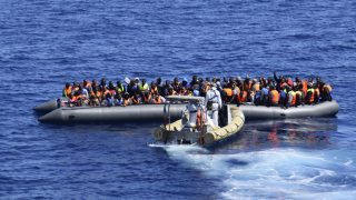 Migrants sit in their boat during a rescue operation by Italian Navy vessels off the coast