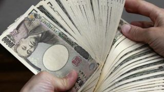A bank teller counts ¥10,000 bank notes in Tokyo. (Photo: AFP/Yoshikazu Tsuno)