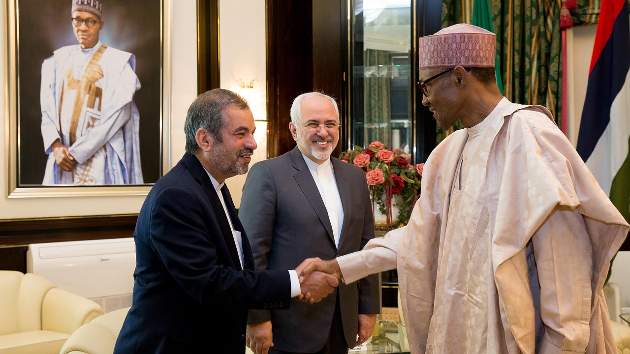 Nigerian President Mohammadu Buhari (R) shakes hand with Iran Ambassador to Nigeria Morteza Rahimi Zarchi, while Iranian Foreign Minister Mohammad Javad Zarif (C) stands during their visit to the presidency in Abuja, on July 25, 2016. Iran Foreign Minister Mohammad Javad Zarif is in Nigeria on the first leg of a four-nation tour of West Africa, which will take him to Ghana, Guinea-Conakry and Mali to discuss possible ways of expanding relations with the countries.  STRINGER / AFP
