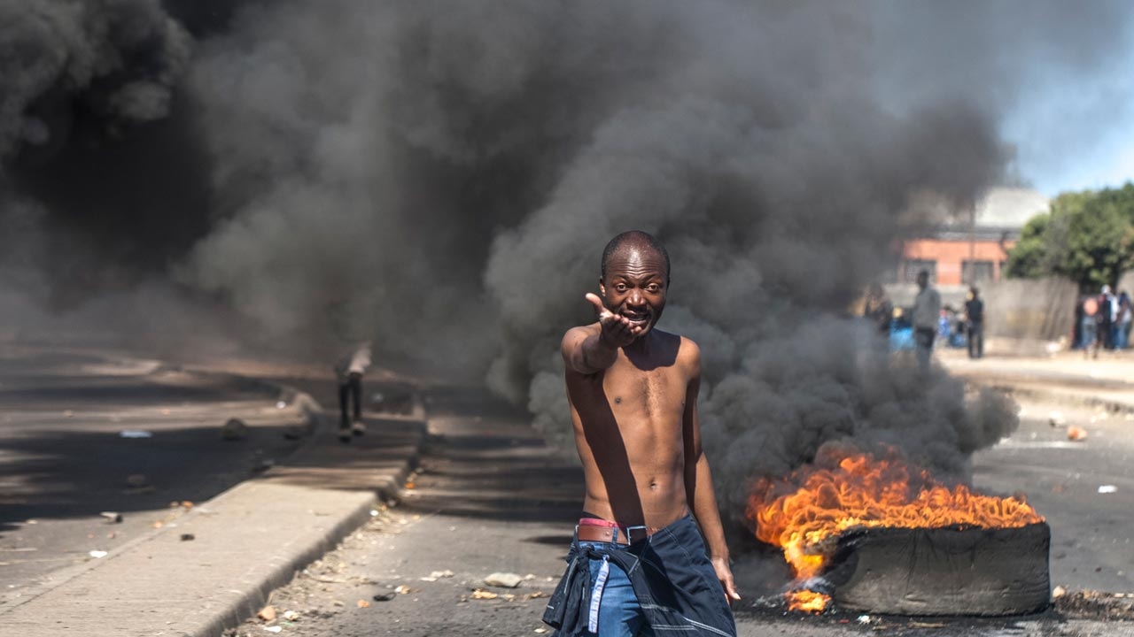 (FILES) This file photo taken on July 06, 2016 shows a protester shouting anti-Mugabe slogans in front of burning tyres during a demonstration on July 6 2016, in Makokoba, Bulawayo Zimbabwe. Street protests, national work boycotts and internet activism are on the rise in Zimbabwe -- offering hints that opposition to ageing President Robert Mugabe could be building towards a boiling point. AFP