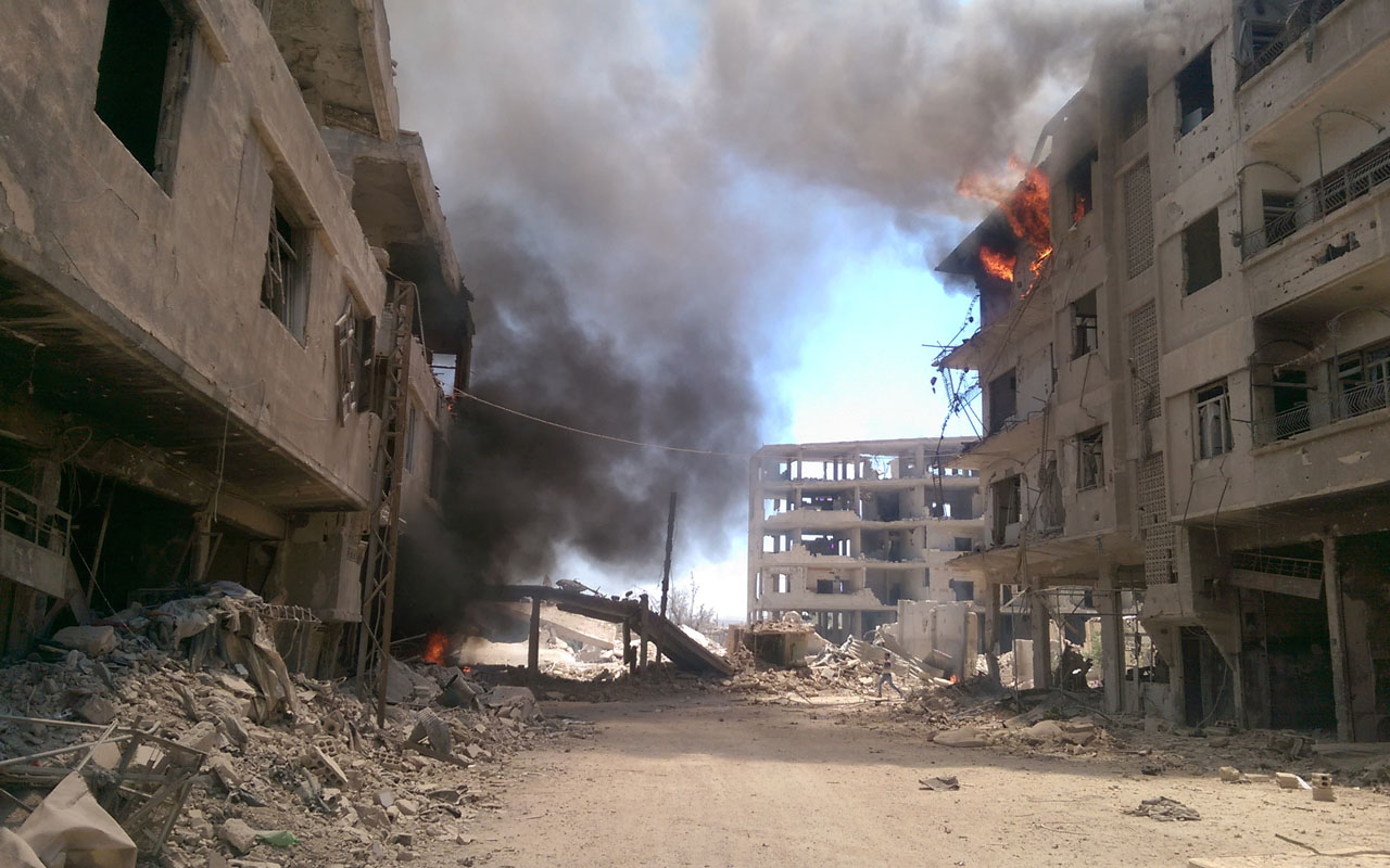 Fire and smoke gush out of buildings following reported air strikes on the Syrian besieged rebel-held town of ?Daraya near the capital Damascus on August 16, 2016.  / AFP PHOTO / FADI DIRANI