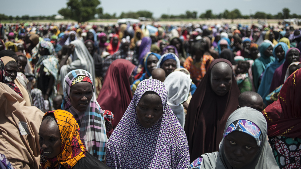In this photo taken on September 15, 2016 women and children queue to enter one of the Unicef nutrition clinics at the Muna makeshift camp which houses more than 16,000 IDPs (internally displaced people) on the outskirts of Maiduguri, Borno State, northeastern Nigeria. AFP PHOTO / STEFAN HEUNIS