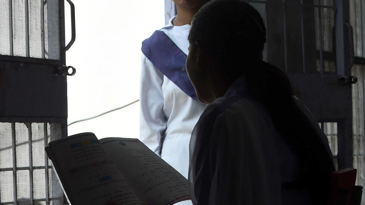 In this photograph taken on September 27, 2016, Esham Masih, daughter of Asia Bibi, a Christian woman facing death sentence for blasphemy, reads a book beside her sister Esha Mashi at a living area in a school building in Lahore. Esham and her sister Esha live largely in seclusion: fears they will be mistreated because they are daughters of the accused in Pakistan's most infamous blasphemy case make them reluctant to venture into the brimming back streets of Lahore. PHOTO: ARIF ALI / AFP
