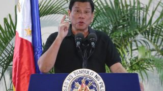 "Philippines President Rodrigo Duterte delivers a speech at the Davao international airport terminal building early on September 30, 2016, shortly after arriving from an official visit to Vietnam. Duterte on September 30 drew a parallel with his deadly crime war and Hitler's massacre of Jews, as he said he was ""happy to slaughter"" millions of drug addicts. MANMAN DEJETO / AFP"