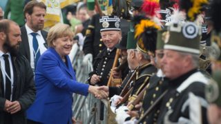 German Chancellor Angela Merkel shakes hands with wellwishers dressed in historic coal miner uniforms as she arrives to attend festivities to celebrate the Day of German Unity in Dresden, eastern Germany, on October 3, 2016. Dresden, a Baroque city in Germany's ex-communist east, is hosting national celebrations to mark 26 years since the reunification of East and West Germany. Sebastian Kahnert / DPA / AFP