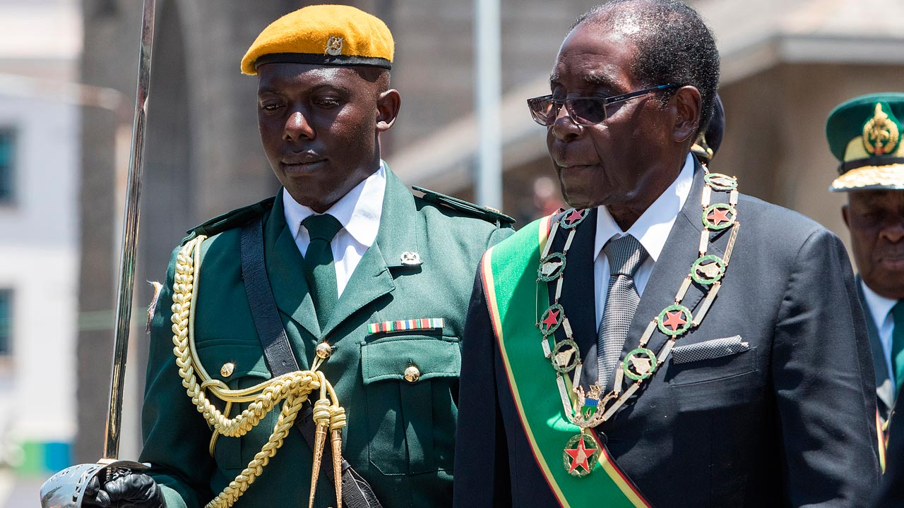 Zimbabwe's President Robert Mugabe (R) inspects an honor guard during the official opening of the fourth session of the eight Parliament of Zimbabwe on October 6, 2016 in Harare. Zimbabwean President Robert Mugabe on October 6 said parliament would tone down the controversial equity law which has been blamed for scaring off potential investors from the crisis-ridden economy. Mugabe also bemoaned the worsening economic woes that have sparked a spate of nationwide protests in recent months. PHOTO: Jekesai Njikizana / AFP