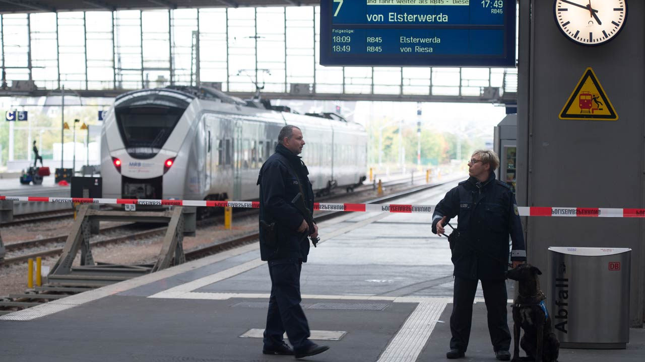 """Policemen secure the area on a platform of the train station in Chemnitz, eastern Germany, on October 8, 2016. Two persons were arrested at the train station in connection with the case of a Syrian suspected of planning a bomb attack. German police found """"highly explosive"""" materials in the apartment of the wanted man who still is the target of a manhunt. Arno Burgi / dpa / AFP"""