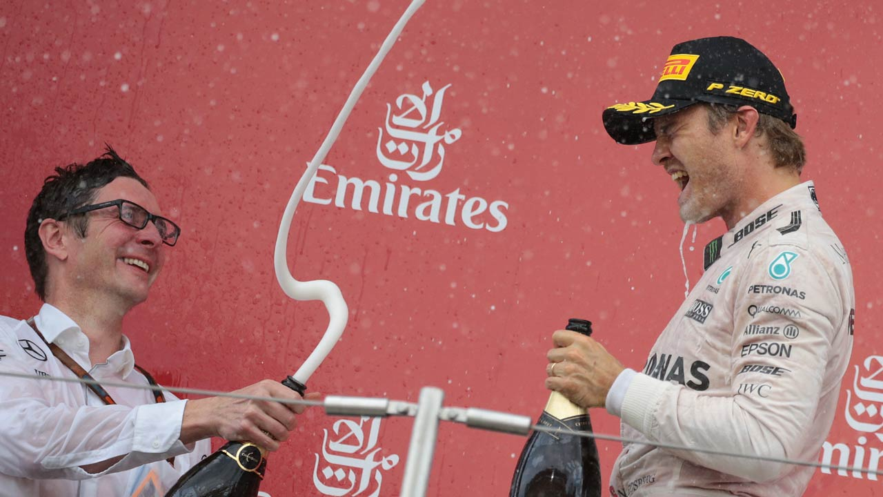 Mercedes AMG Petronas F1 Team's German driver Nico Rosberg celebrates his victory on the podium with his team engineer Andrew Shovlin (L) after the Formula One Japanese Grand Prix at the Suzuka Circuit on October 9, 2016.  YUYA SHINO / AFP