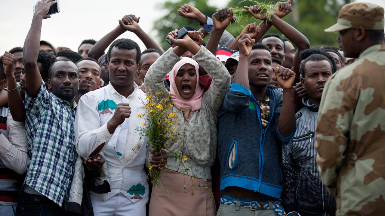 """(FILES) This file photo taken on October 2, 2016 shows residents of Bishoftu crossing their wrists above their heads as a symbol for the Oromo anti-government protesting movement during the Oromo new year holiday Irreechaa in Bishoftu. Ethiopia declared a state of emergency on October 9, 2016 following months of violent anti-government protests, according to an official statement. """"The state of emergency was declared following a thorough discussion by the Council of Ministers on the loss of lives and property damages occurring in the country,"""" Prime Minister Hailemariam Desalegn said. Zacharias ABUBEKER / AFP"""