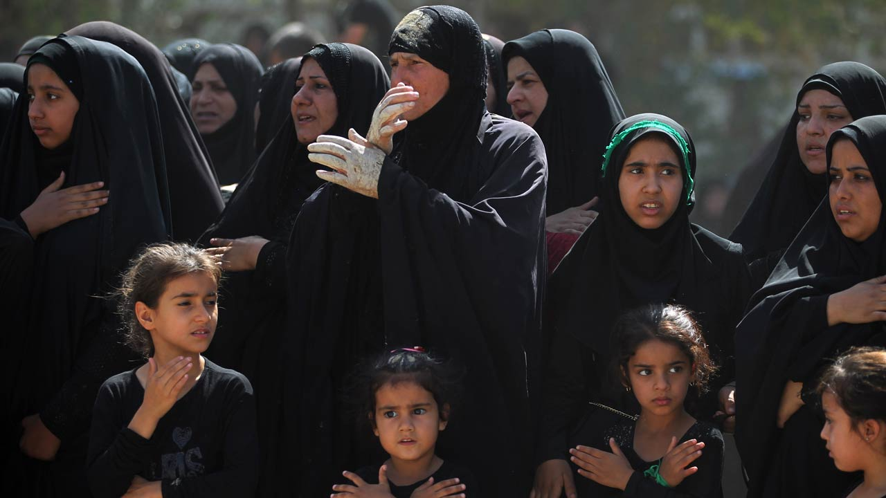 Iraqi Shiite Muslim women and children watch a reenactment of the Battle of Karbala as part of the Ashura commemorations in Baghdad on October 12, 2016. Ashura mourns the death of Imam Hussein, a grandson of the Prophet Mohammed, who was killed by armies of the Yazid near Karbala in 680 AD. AHMAD AL-RUBAYE / AFP