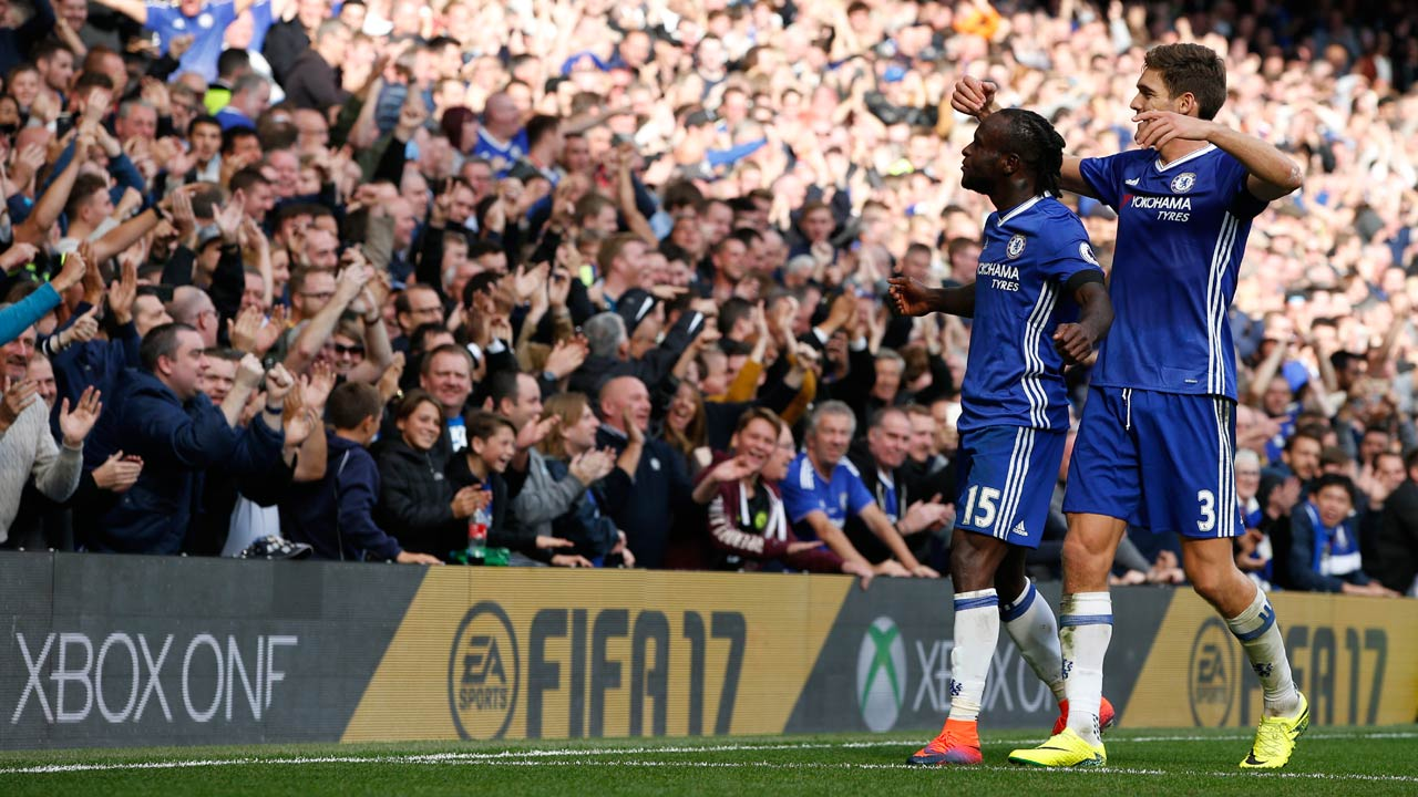 Chelsea's Nigerian midfielder Victor Moses (L) celebrates with Chelsea's Spanish defender Marcos Alonso after scoring their third goal during the English Premier League football match between Chelsea and Leicester City at Stamford Bridge in London on October 15, 2016.  Adrian DENNIS / AFP