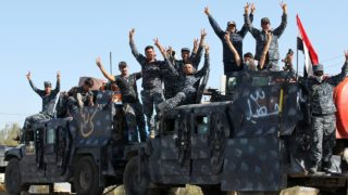 Iraqi forces gesture as they gather at the Qayyarah military base, about 60 kilometres (35 miles) south of Mosul, on October 16, 2016, as they prepare for an offensive to retake Mosul, the last IS-held city in the country, after regaining much of the territory the jihadists seized in 2014 and 2015.  AHMAD AL-RUBAYE / AFP
