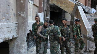 "Syrian pro-government soldiers chat as they advance in Aleppo's rebel-held Bustan al-Basha neighbourhood on October 6, 2016. ""Syrian regime forces advanced from the city centre north into (rebel-held) Bustan al-Basha, and seized a large athletic complex there,"" the UK-based Syrian Observatory for Human Rights said. This was the first time the regime had entered the district since 2013 and there had been fierce clashes, they added.      This was the first time the regime had entered the district since 2013 and there had been fierce clashes, he added.   / AFP PHOTO / GEORGE OURFALIAN"