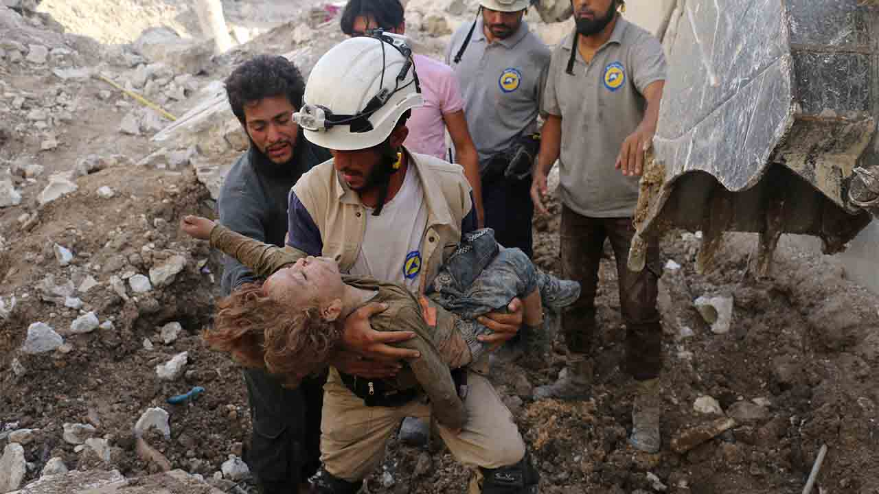 A Syrian civil defence volunteer, known as the White Helmets, holds the body of a child after he was pulled from the rubble following a government forces air strike on the rebel-held neighbourhood of Karm Homad in the northern city of Aleppo, on October 4, 2016. Syrian regime forces advanced against rebels during intense street battles in the heart of Aleppo, after the United States abandoned talks with Russia aimed at reviving a ceasefire deal.  / AFP PHOTO / AMEER ALHALBI