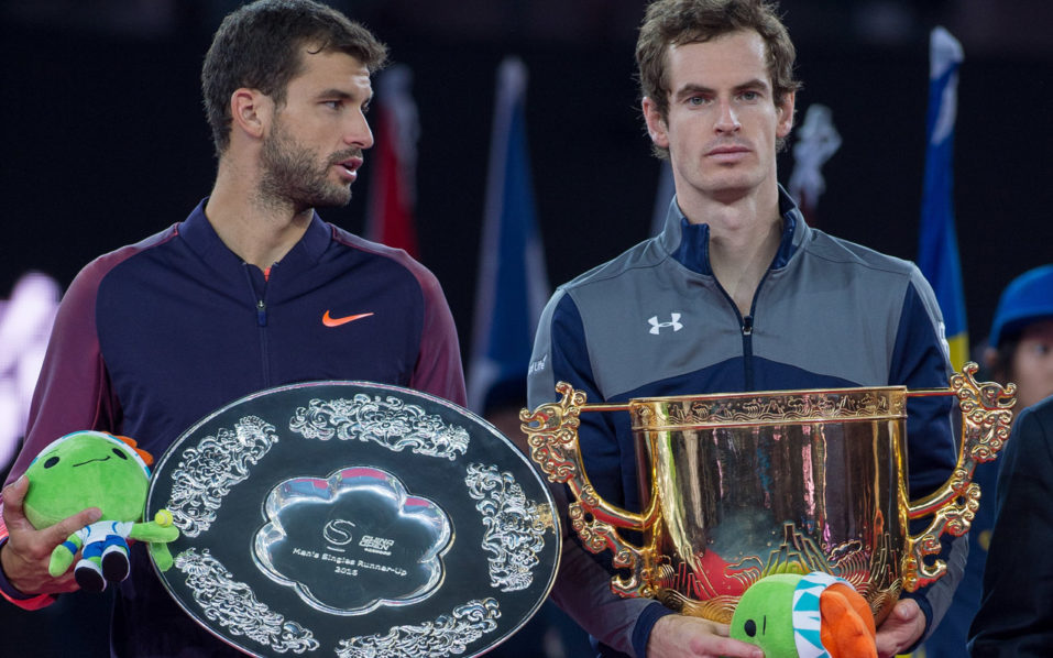 Andy Murray of Britain (R) celebrates with the trophy as he wins against Grigor Dimitrov (L) of Bulgaria in their men's singles final match of the China Open tennis tournament in Beijing on October 9, 2016. / AFP PHOTO / NICOLAS ASFOURI