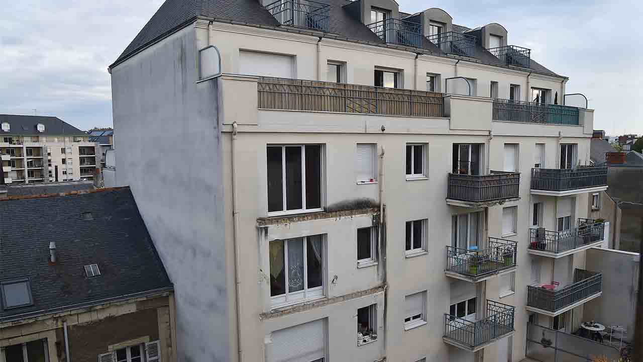 """A picture taken on October 16, 2016 shows the rear side of a building in which four people were killed and several others injured after a balcony collapsed, in Angers, northwestern France. Four people died and more than a dozen others were injured, some of them """"seriously"""" but not in danger of death, after the collapse of a balcony in the building, according to the prefecture and hospital. A dozen people stood on the balcony on the third floor of the recently constructed building, when the accident occurred shortly before midnight on October 15. The balcony collapsed for an unknown reason, causing the balconies of the two lower floors to collapse as well, but according to sources close to the investigation, no one was on the lower balconies. / AFP PHOTO / JEAN-FRANCOIS MONIER"""