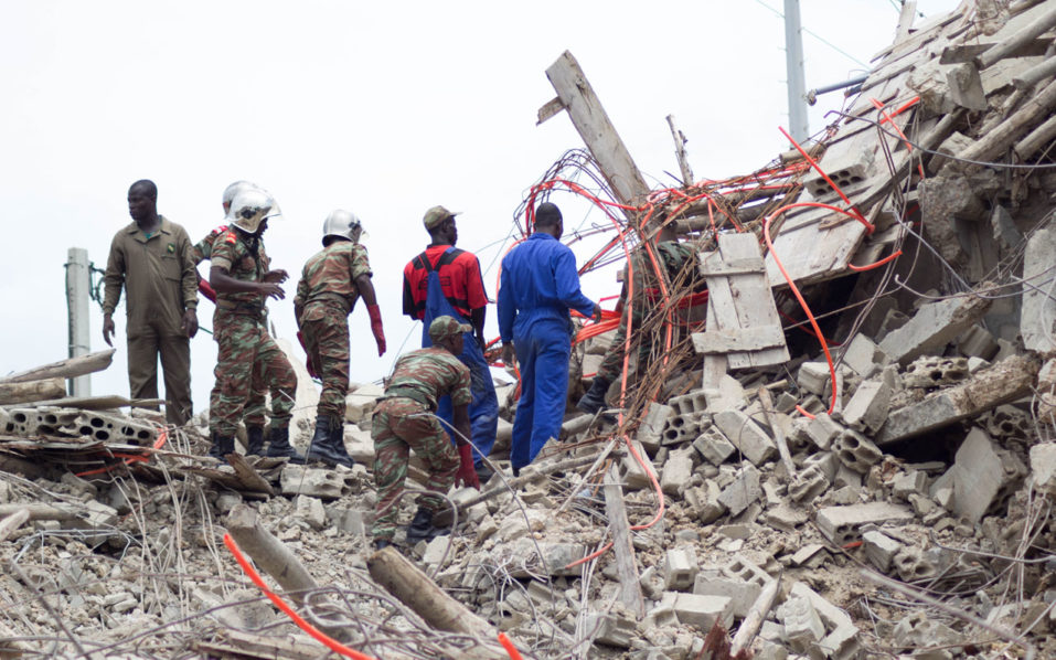 Rescue workers look for survivors after a building collapsed  killing at least three people in Cotonou on October 6, 2016.  / AFP PHOTO / YANICK FOLLY