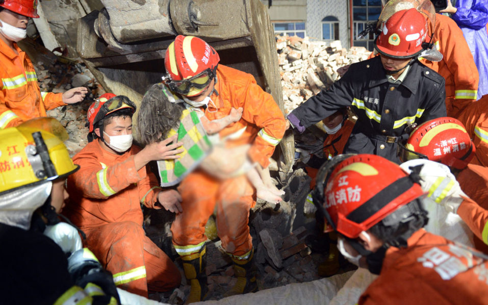 This picture taken on October 10, 2016 shows rescuers carrying a young girl who was rescued at an accident site after four buildings caved in during the early hours in Wenzhou, eastern China's Zhejiang province. A series of multi-storey buildings built by local villagers and packed with migrant workers collapsed in China on October 10, killing at least 20 people, the government and reports said. / AFP PHOTO / STR / China OUT