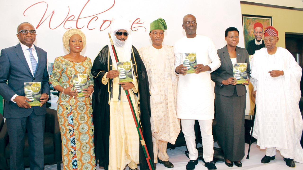 Mr. Oyetunji (left); author, Funmi Oyetunji; Emir Sanusi, Chief Ogunshola, Adeniyi, David-Borha and Chief Akinkugbe… at the presentation ceremony in Lagos