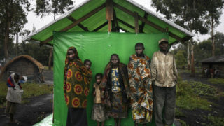 a group of pygmies shelter from the rain in Mubambiro village near Goma, Democratic Republic of Congo.  At least 20 people have been killed in three days of clashes in southeast DR Congo between Pygmy and Bantu people over a disputed caterpillar collection tax, a local parliamentarian told AFP on October 18, 2016. Local MP Kalunga Mawazo told AFP on October 18 that the fighting in Kabalo between October 16 and 18 was triggered by a dispute over the caterpillar harvest, a common food staple for the hunter-gatherer people of the Tanganyika region in northern Katanga.  / AFP PHOTO / Jose CENDON