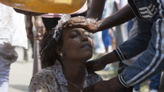 Men wash the face of a woman after police used teargas during the Oromo new year holiday Irreechaa in Bishoftu on October 2, 2016. Several people were killed in a stampede near the Ethiopian capital on October 2, according to an AFP photographer at the scene. Several thousand people from the Oromo community gathered at a sacred lake for a religious festival and started to cross their wrists above their heads, a symbol of Oromo anti-government protests. The event quickly degenerated, with protesters throwing stones and bottles and security forces responding with baton charges and tear gas grenades. Together, Oromos and Amharas make up 60 percent of the population and have become increasingly vocal in rejecting what they see as the disproportionate power wielded by the northern Tigrean minority in government and the security forces. / AFP PHOTO / Zacharias ABUBEKER