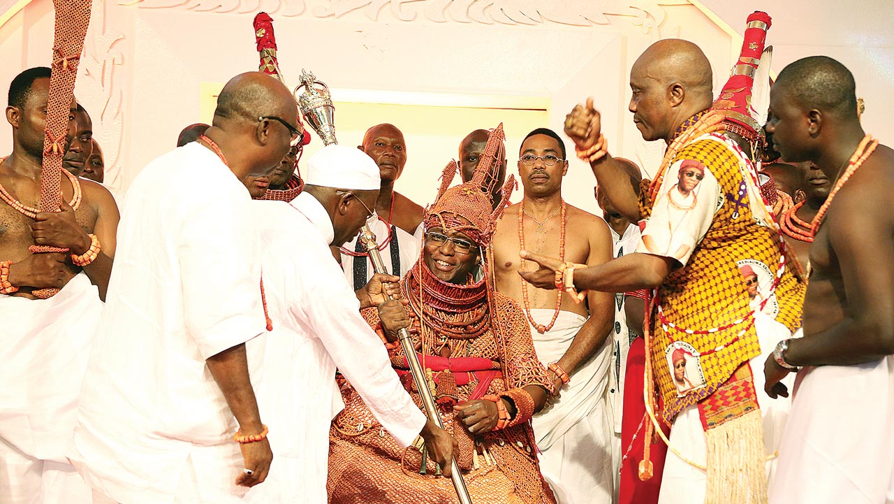 Edo State Governor Adams Oshiomhole (second left) presents the staff of office to His Royal Majesty, Omo n'Oba n'Edo Uku Akpolokpolo, Oba Ewuare II, Oba of Benin after his coronation …