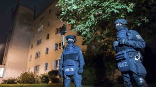 "Policemen in protective cllothing stand in front of at a residential building in Chemnitz, eastern Germany, on October 8, 2016. Police found several hundred grams of ""explosive materials"" in the east German apartment of a Syrian man suspected of planning a bomb attack, and arrested three people connected to him. The suspect who remains at large, 22-year-old Syrian Jaber Albakr, could have had ""an Islamist motive"" sources close to the police told AFP.  / AFP PHOTO / Jens-Ulrich Koch"