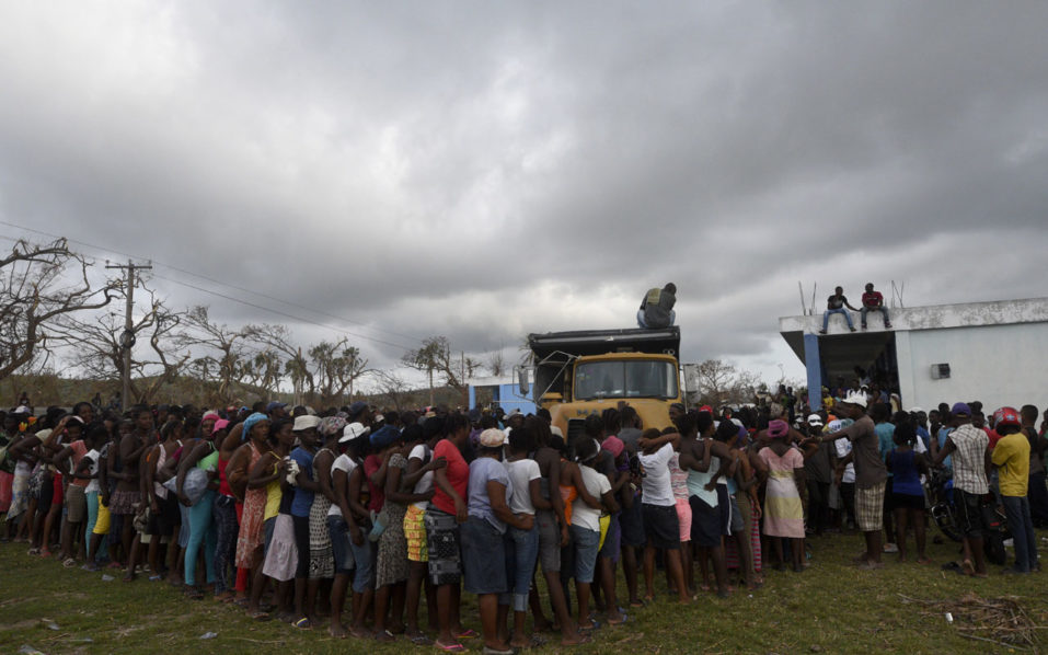 People queue for food and clothes being distributed at a shelter in Port-Salut, southwest of Port-au-Prince, on October 9, 2016, days after the passage of Hurricane Matthew through Haiti. Haiti began three days of mourning on Sunday for hundreds killed in Hurricane Matthew as relief officials grappled with the unfolding devastation in the Caribbean country's hard-hit south. And nearly a week after being devastated by the hurricane, Haiti is confronted with a growing cholera outbreak threatening to turn its disaster even more deadly. / AFP PHOTO / RODRIGO ARANGUA