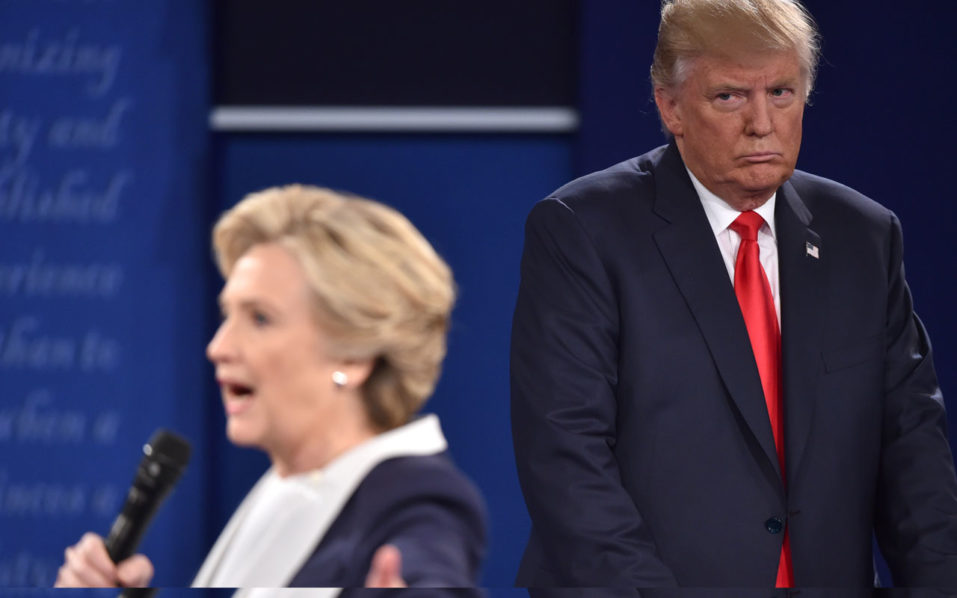 "(FILES) This file photo taken on October 9, 2016 shows Republican presidential candidate Donald Trump as he listens to Democratic presidential candidate Hillary Clinton during the second presidential debate at Washington University in St. Louis, Missouri. Hillary Clinton has accused her Republican presidential rival Donald Trump of ""stalking"" her during their televised debate on October 9, 2016. Trump often stood closely behind the Democratic nominee glowering as she answered questions from the audience during the town hall-style event in St. Louis. Speaking during an interview on NBC's The Ellen DeGeneres Show set to air October 14, 2016, Clinton said his movements made her feel ""really weird"" on stage. / AFP PHOTO / Paul J. Richards"
