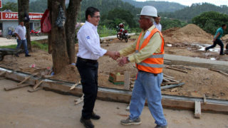 Photo released by the Honduran Presidency of Honduran President Juan Orlando Hernandez (L) shaking hands with a construction worker in Campamento, Olancho department, Honduras, on October 13, 2016.  Honduran authorities are investigating an alleged drug traffickers' plan against Hernandez and US Ambassador in Tegucigalpa James Nealon. / AFP PHOTO / Honduran Presidency / HO /