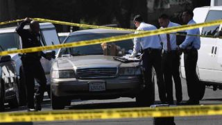 Police and investigators at the scene where three people killed during a shooting after a dispute at at a pop-up Jamaican restaurant in Los Angeles on October 15, 2016. Three people were killed and at least a dozen more injured, police said Saturday. One person has been arrested and police have launched a manhunt for another in connection with the deadly incident in West Adams, in the southwestern part of the metro area, said spokesman Lieutenant Chuck Springer.   / AFP PHOTO / Mark RALSTON