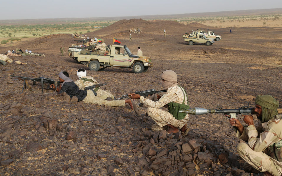 Tuaregs fighters of the Coordination of Movements of the Azawad (CMA) stand with weapon near pick up trucks with machine gun near Kidal, northern Mali on September 28, 2016, where rival groups have clashed in recent weeks over the country's shaky peace deal. The most recent fighting -- between pro-government group GATIA and ex-rebels from the Coordination of Azawad Movements (CMA) -- left around a dozen fighters dead on September 16 near the northeastern city. / AFP PHOTO / STRINGER