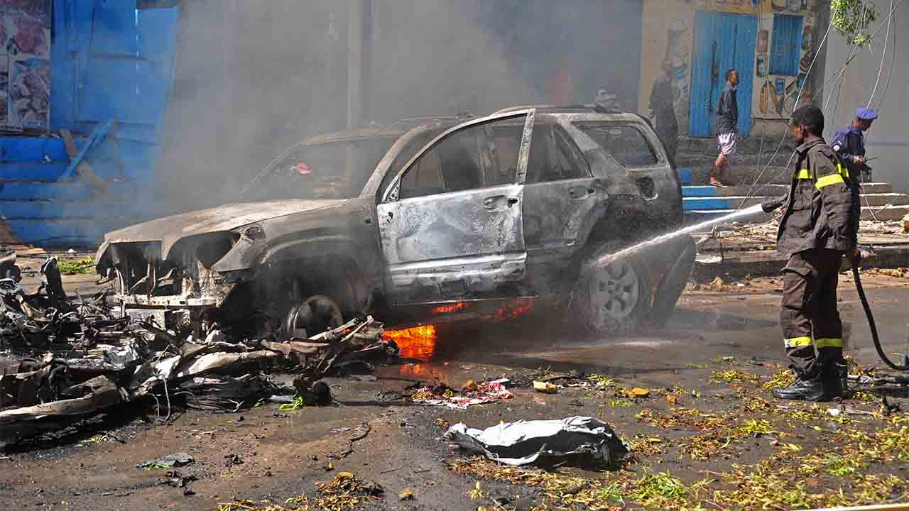 Firefighters douse the flaming wreckage of car after a suicide car bomb attack in Mogadishu on October, 1, 2016. At least two people were killed and five injured October 1 when a car loaded with explosives blew up near a restaurant in Mogadishu, a security official and witnesses said. The car was parked in front of the Blue Sky restaurant, near a busy road close to the headquarters of the Somali National Intelligence and Security Agency (NISA) in a southern district of the city. / AFP PHOTO / Mohamed ABDIWAHAB