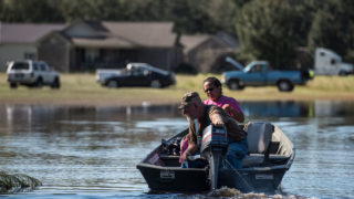 A man and woman land a boat on a front yard on October 10, 2016 in Lumberton, North Carolina. The death toll from Hurricane Matthew in the U.S. has climbed to over 20.   Sean Rayford/Getty Images/AFP