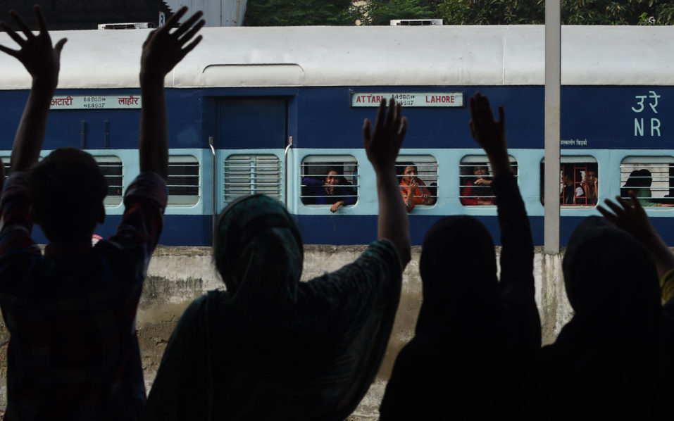 """Pakistani relatives wave towards Indian travelers as they leave on the India-bound Samjhota Express from Lahore Railway Station in Lahore on September 26, 2016. The Samjhota Express train service, which runs between New Delhi and Lahore, has resumed a few hours after its suspension by Indian authorities. Indian Prime Minister Narendra Modi lashed out at Pakistan September 24 accusing it of """"exporting terrorists"""" after a deadly attack on an army base that New Delhi has blamed on Pakistan-based militants. Modi's comments were the latest in a war of words between the neighbours over escalating tensions in disputed Kashmir, where 18 Indian soldiers were killed last week in the worst attack in the region for over a decade. / AFP PHOTO / ARIF ALI"""
