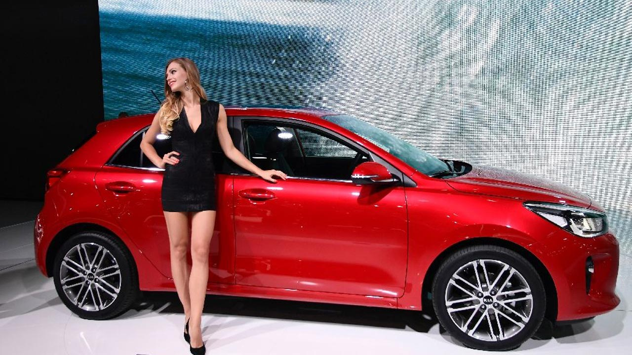 A hostess presents the new Kia Rio during the Paris Motor Show on September 30, 2016 PHOTO: AFP/ Miguel Medina
