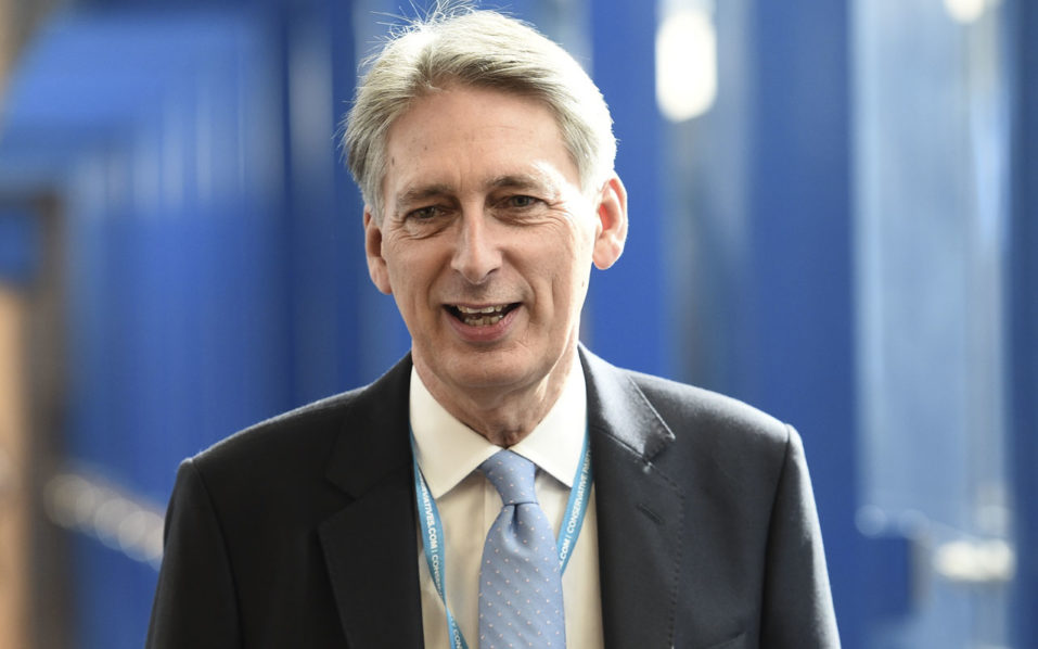 British Chancellor of the Exchequer Philip Hammond walks along the bridge from the hotel to the International Convention Centre in Birmingham, central England, on October 2, 2016 on the first day of the Conservative party annual conference. Britain's governing Conservative Party meets for its annual conference from Sunday facing questions over how and when it will take the country out of the European Union following the Brexit vote. / AFP PHOTO / OLI SCARFF