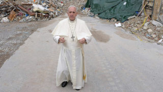 This handout picture released by the Vatican press office on October 4, 2016 shows Pope Francis during a visit in Amatrice, Italy.  Pope Francis on October 4, 2016 made a surprise visit to Amatrice, the small Italian mountain town that bore the brunt of the August 24 earthquake that killed nearly 300 people. The Argentinian pontiff's first point of call was a set of colourful pre-fabricated buildings serving as a makeshift school. Amatrice's school was destroyed in the quake despite having been expensively renovated to make it quake resistant a few years ago / AFP PHOTO / OSSERVATORE ROMANO / OSSERVATORE ROMANO