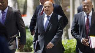 """South Africa's Minister of Finance Pravin Gordhan (C), walking out from the Finance Ministry with officials up to the South African Parliament to deliver the 2016 Budget Speech, in Cape Town.  South African Finance Minister Pravin Gordhan will be prosecuted for fraud over alleged misconduct when he was head of the South African Revenue Service (SARS), officials said on October 11, 2016, in a move set to shake the country's fragile economy. Gordhan and two others """"must be prosecuted and arraigned on the following crimes: count one, fraud,"""" Shaun Abrahams, head of the National Prosecuting Authority (NPA), told reporters.  / AFP PHOTO / RODGER BOSCH"""