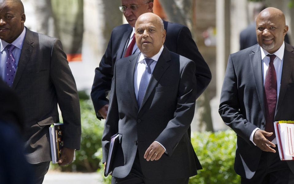 "South Africa's Minister of Finance Pravin Gordhan (C), walking out from the Finance Ministry with officials up to the South African Parliament to deliver the 2016 Budget Speech, in Cape Town. South African Finance Minister Pravin Gordhan will be prosecuted for fraud over alleged misconduct when he was head of the South African Revenue Service (SARS), officials said on October 11, 2016, in a move set to shake the country's fragile economy. Gordhan and two others ""must be prosecuted and arraigned on the following crimes: count one, fraud,"" Shaun Abrahams, head of the National Prosecuting Authority (NPA), told reporters. / AFP PHOTO / RODGER BOSCH"