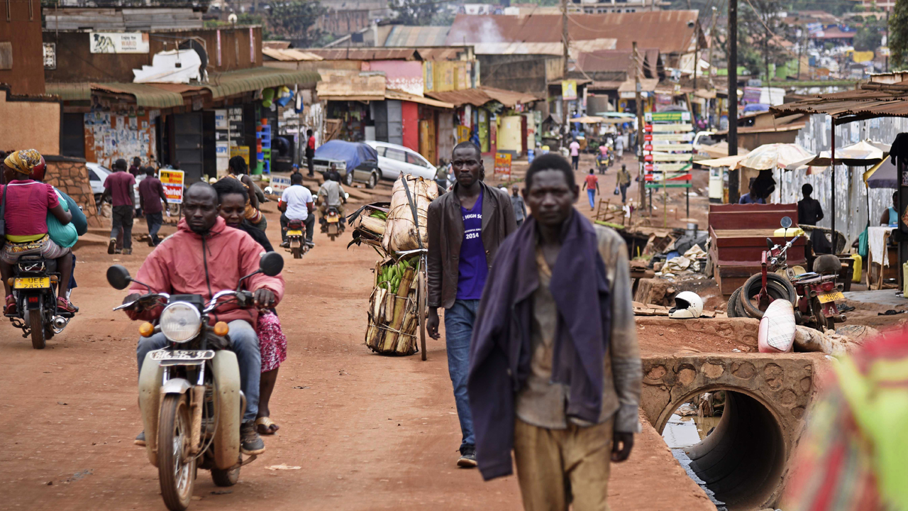 """Brian Mugabi (C), brother to Phiona Mutesi, walks along a street in Katwe, a Kampala suburb, on September 29, 2016. Standing on a drab side-street next to an open sewer in the Ugandan capital Kampala, Brian Mugabi points to the site of his former family home and reflects on how much the game of chess has changed their lives. The family's story is now the basis for the feel-good Disney movie """"Queen of Katwe"""" which premiered in Uganda last weekend with Oscar-winning Kenyan actress Lupita Nyong'o playing the role of Phiona's mother. PHOTO: AFP/ ISAAC KASAMANI"""