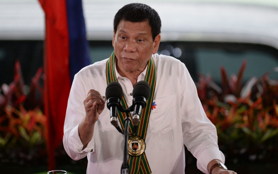 """Philippine President Rodrigo Duterte gestures as he delivers a speech during a """"talk to the troops"""" visit to meet military personnel in Manila on October 4, 2016. Rodrigo Duterte launched a fresh tirade at the United States on October 4, telling Barack Obama to """"go to hell"""" as the longtime allies launched war games that the firebrand Philippine leader warned could be their last. / AFP PHOTO / TED ALJIBE"""