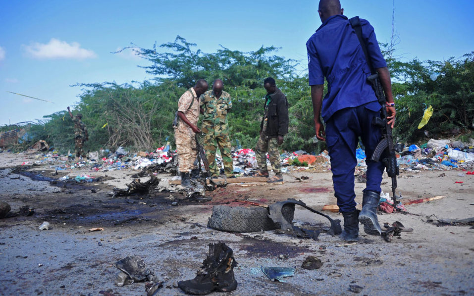 Members of the Somalian military forces stand at the site of a suicide car bomb attack, The attack was claimed by the Al-Qaeda linked Shabaab. / AFP PHOTO / Mohamed ABDIWAHAB