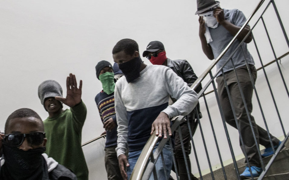 Masked students enter a building of the Witwatersrand University in Johannesburg on October 10, 2016 to disrupt classes in a bid to shut down the campus. Student protesters at South Africa's prestigious Wits University forced their way into lecture halls and caused many lessons to be abandoned Monday, ratcheting up pressure in a battle over tuition fees. Violent clashes with police have erupted regularly on campuses across the country in recent months, and several universities have been closed to avoid further unrest. / AFP PHOTO / MARCO LONGARI
