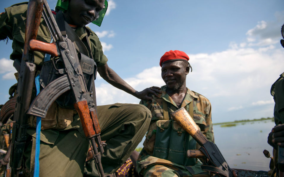 """Sudan People Liberation Army (SPLA) soldiers ride on a boat on the Nile river on their way to Aleleo, Fashoda State, on October 16, 2016, after the SPLA accused the opposition forces of attacking their defensive positions in the area. Heavy fighting broke out on October 14 between SPLA (Government) and opposition forces in Wajwok and Lalo villages, outside Malakal. SPLA commanders claim they succeeded to keep their positions and assure their forces just responded """"on self defence."""" Opposition forces lost over 56 soldiers and the SPLA recovered more than 200 guns, but the SPLA also suffered casualties of 4 deaths and 22 wounded soldiers in both attacks. / AFP PHOTO / Charles Atiki Lomodong"""