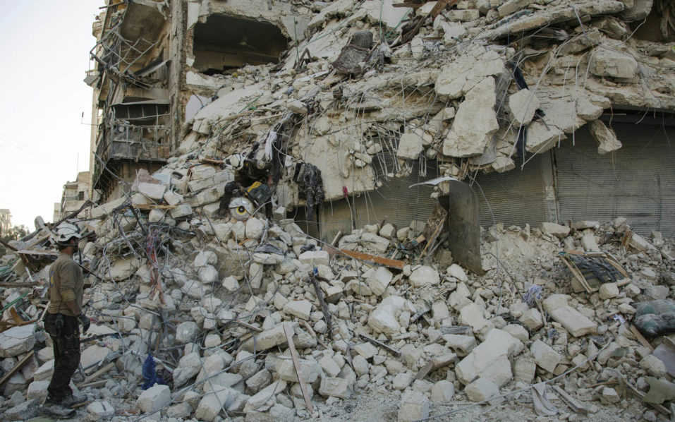 A member of the Syrian Civil Defence, known as the White Helmets, stands amid the rubble of a destroyed building during a rescue operation following reported air strikes in the rebel-held Qatarji neighbourhood of the northern city of Aleppo, on October 17, 2016. Dozens of civilians were killed as air strikes hammered rebel-held parts of Aleppo early morning, despite Western warnings of potential sanctions against Syria and Russia over attacks on the city. Both Russian and Syrian warplanes are carrying out air strikes over Aleppo in support of a major offensive by regime forces to capture rebel-held parts of the northern city. / AFP PHOTO / KARAM AL-MASRI