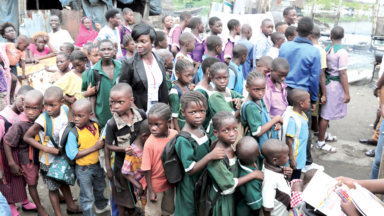 "Pupils of public and private schools in Ajegunle community, Lagos State, being handed exercise books and writing materials by two non-governmental organisations, Dream from the Slum Initiative, and Transform A Life Initiative, as part of their ""Back-To-School"" programme."