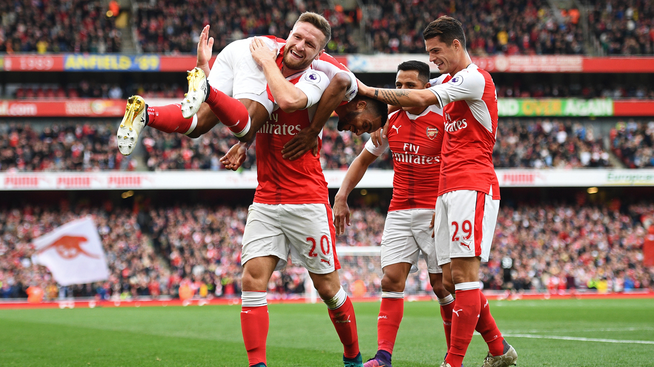 Arsenal's English midfielder Theo Walcott (L) celebrates with Arsenal's German defender Shkodran Mustafi (2nd L) Arsenal's Chilean striker Alexis Sanchez (2nd R) and Arsenal's Swiss midfielder Granit Xhaka (R) after scoring their second goal during the English Premier League football match between Arsenal and Swansea City at the Emirates Stadium in London on October 15, 2016.  Arsenal won the game 3-2. / AFP PHOTO / Justin TALLIS