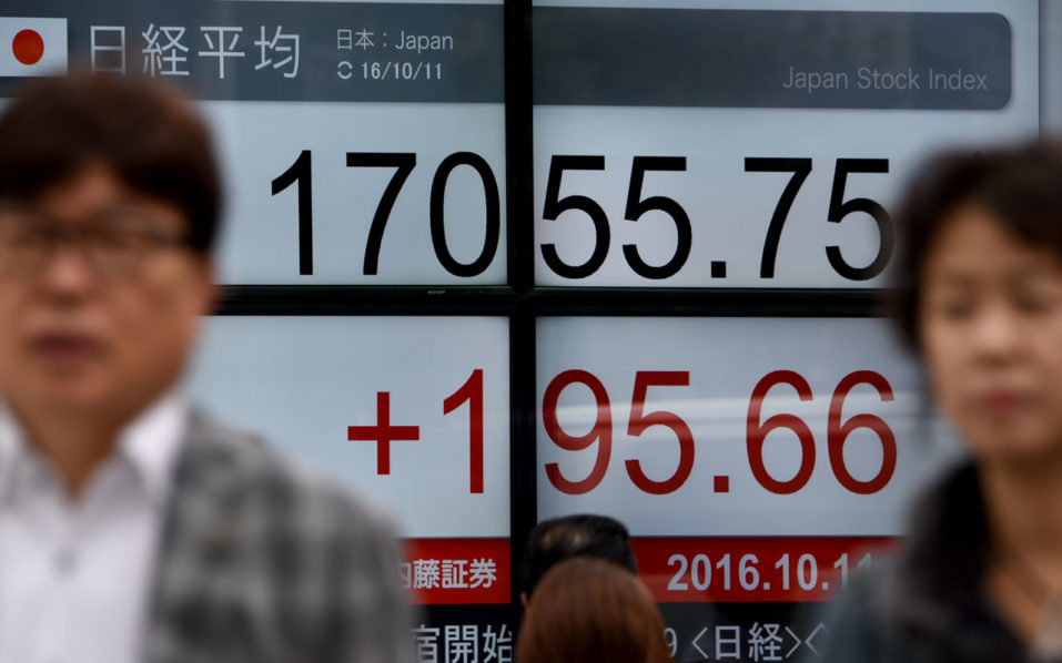 People walk past an electric quotation board flashing the Nikkei key index of the Tokyo Stock Exchange (TSE) in front of a securities company in Tokyo on October 11, 2016.  / AFP PHOTO / TORU YAMANAKA
