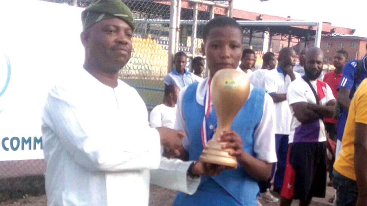 Director General of Lagos State Sports Commission, Mr. Adewunmi Ogunsanya (left), presents the best prize in Ayo board game to Aminu Khadijat of Lafiaji Senior High School at the end of 2-in-1 Traditional Sports Championships for Secondary Schools Students in Lagos… at the weekend.